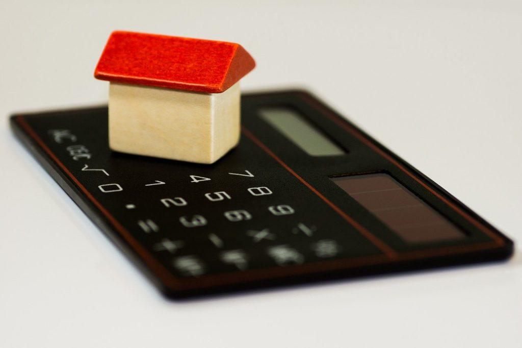 calculatrice avec une maison miniature posée dessus