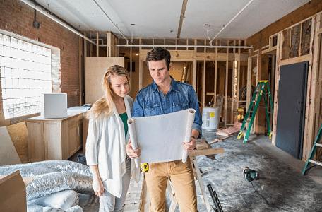 un homme et une femme dans une maison en construction qui regardent les plans