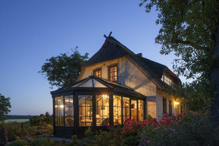 Photo de nuit d'une maison avec véranda